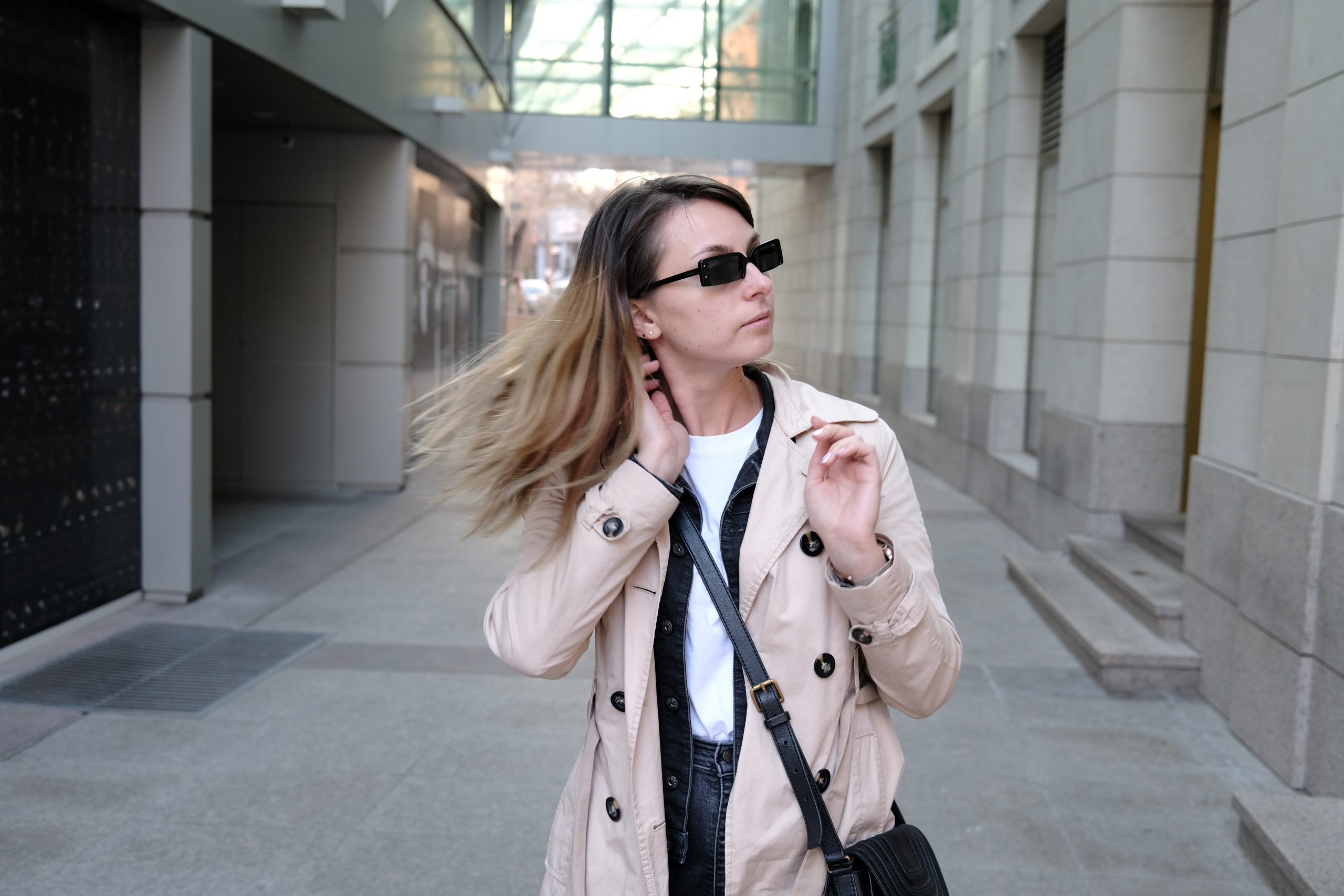 момиче, което развява косата си на вятъра + шлифер